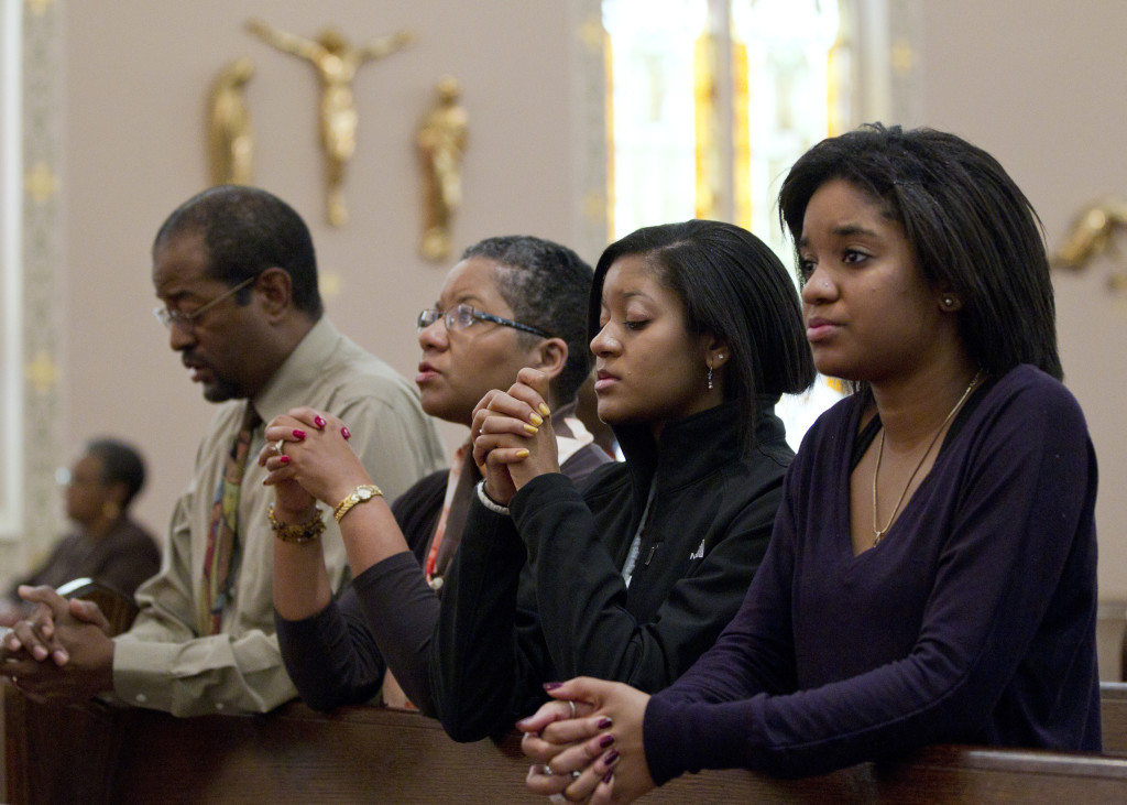 The Brooks family -- Joe, Desiree, Gabrielle and Alyssa -- pray after arriving for Sunday Mass at St. Joseph's Catholic Church in Alexandria, Va., Nov. 27. According to the first study of its kind, Black Catholics in the U.S. are highly engaged with their religion and parish life, more so than white Catholics. (CNS photo/Nancy Phelan Wiechec) (Nov. 29, 2011) See BLACK CATHOLICS Nov. 29, 2011.